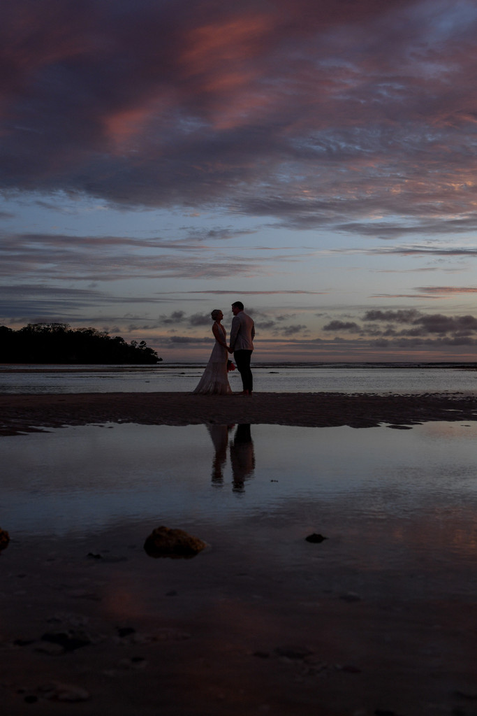 Silhouette of bride and groom in the ocean at dusk