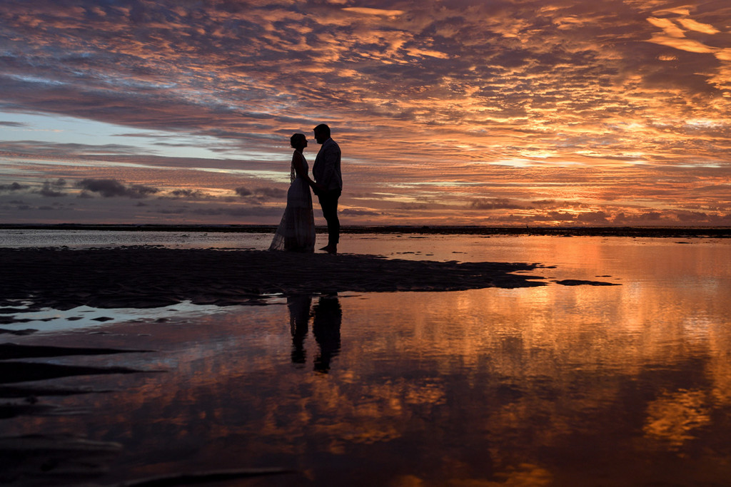 Silhouette of intimate bride and groom against fiery Fiji sunset