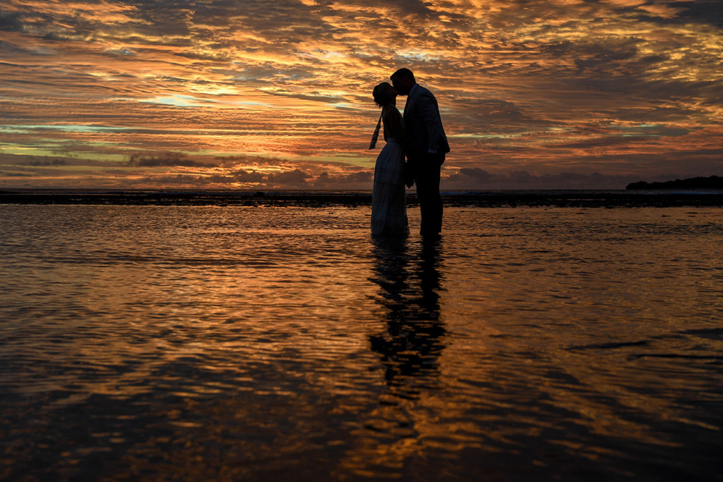 Silhouette of bride and groom kissing in the ocean against golden Fiji sunset