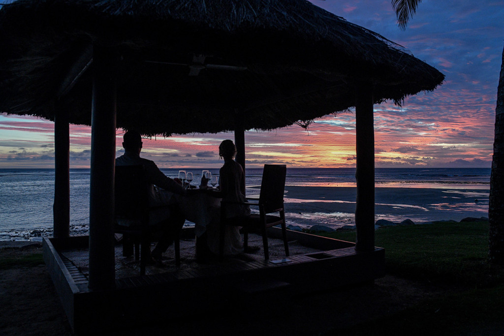 Silhouette of Bride and groom enjoying a romantic dinner at sunset