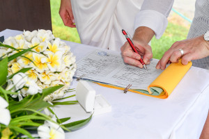 Bride and groom sign their wedding cerfificates