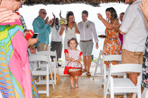 Family and friends cheer as the happily married couple walk down the aisle hand in hand