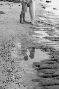 Monochrome reflection of the bride and groom hand in hand on Maui Bay beach
