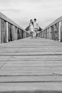 Monochrome picture of the newly married couple strolling hand in hand on the docks