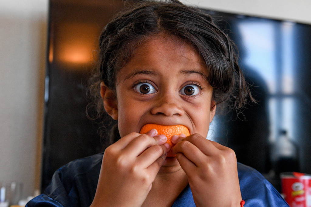 Cute Samoan girl eats an orange