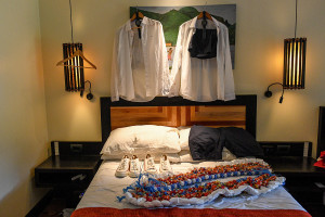 Groomsmen shirts hang in light, sneakers and lei on the bed