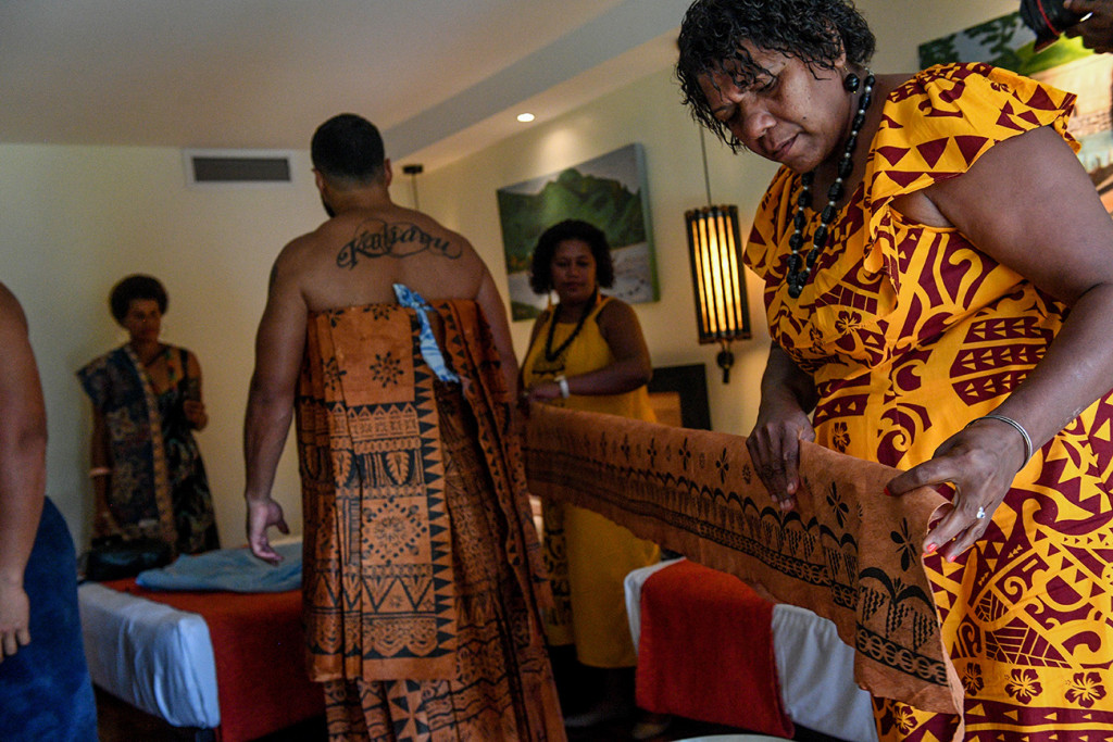 A Samoan mother helps her son tie the Traditional Masi