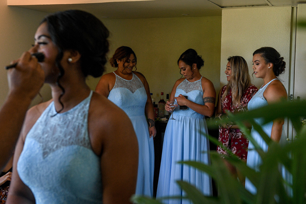 Bridesmaids chat, laugh and drink during wedding preperations
