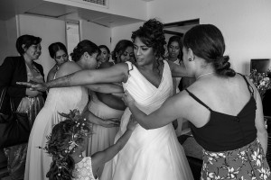 All the bridesmaids help the bride zip her dress