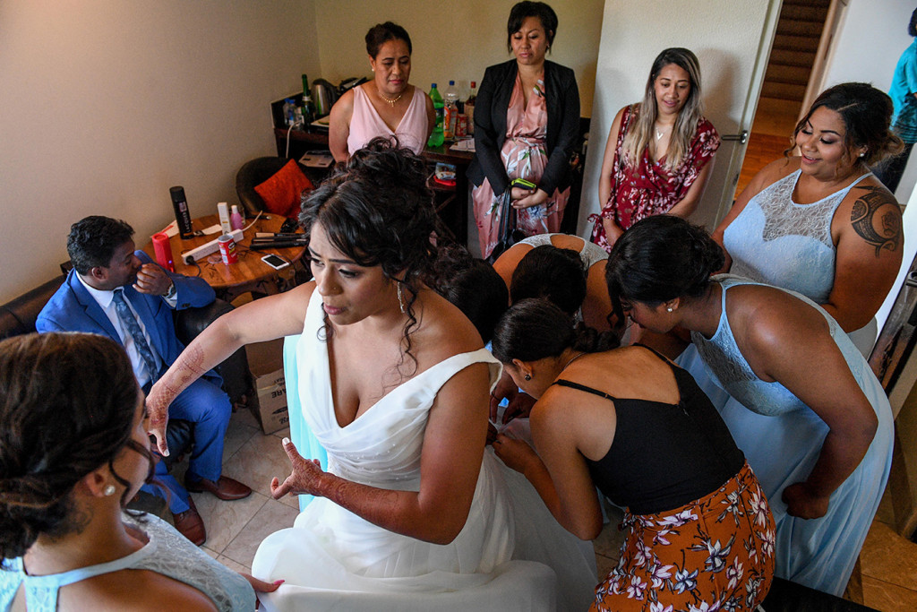 Bridesmaids help the bride fix the hem of her dress