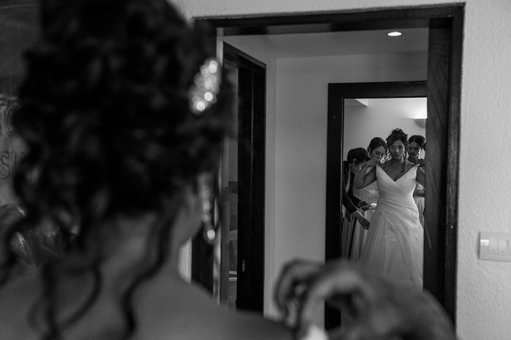 Monochrome photo of the bride admiring her dress by Elegance Marriage in the mirror