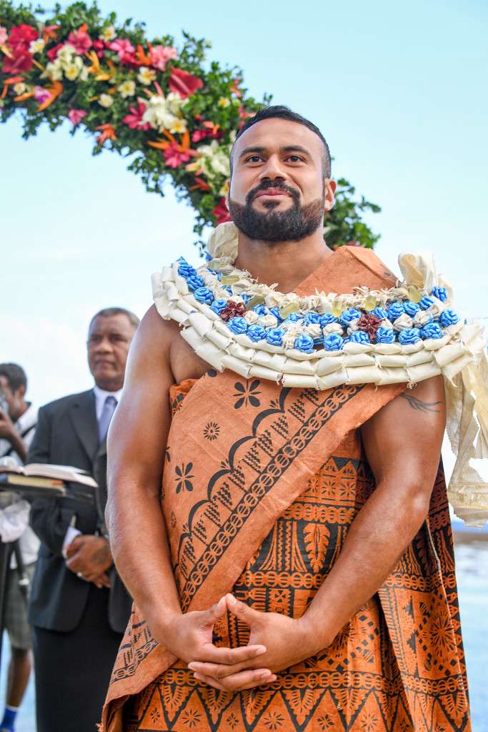 A happy groom in Traditional Samoan Masi and Lei waits at the end of the aisle