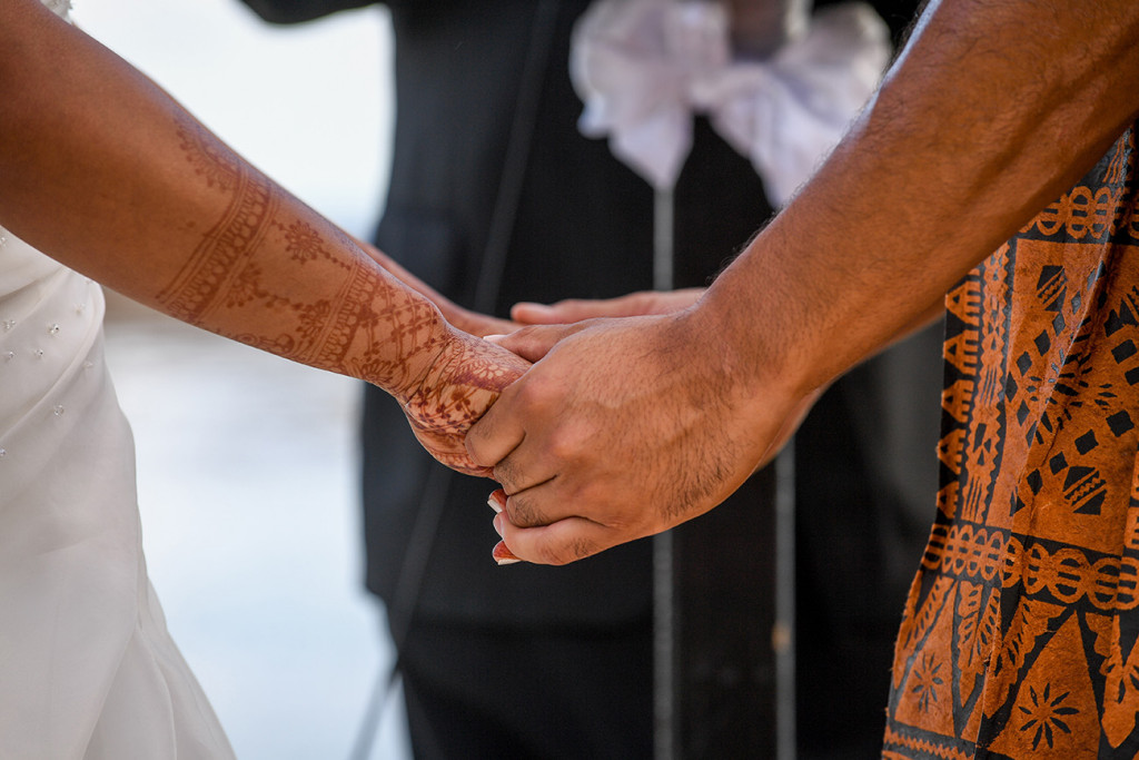 Bride and groom hold hands at the altar
