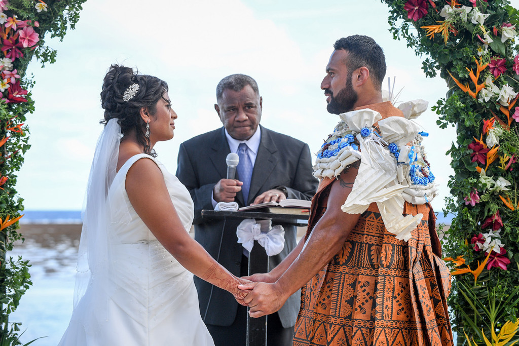 The groom holds his bride's hands as he says his vows