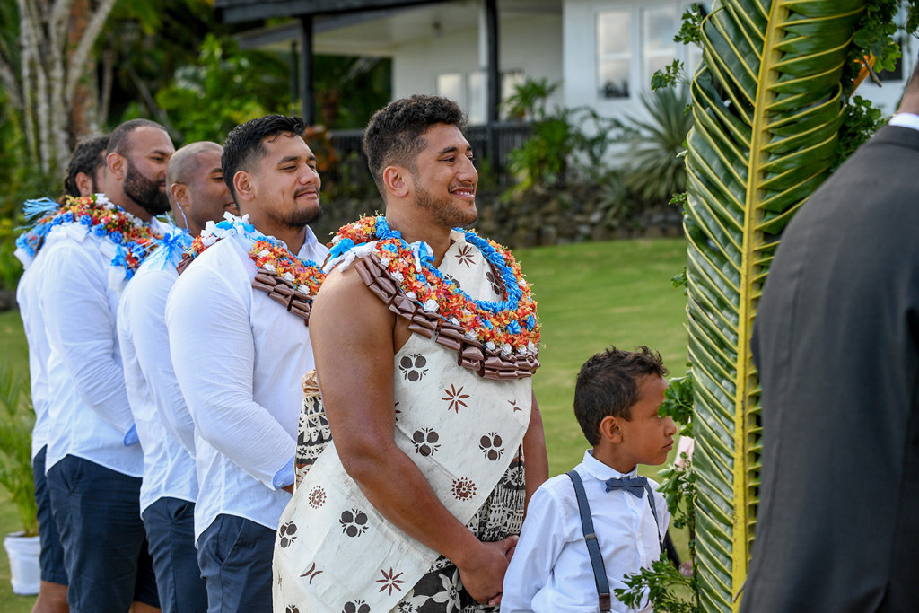 Groomsmen and bestman smile as they watch the couple exchange vows