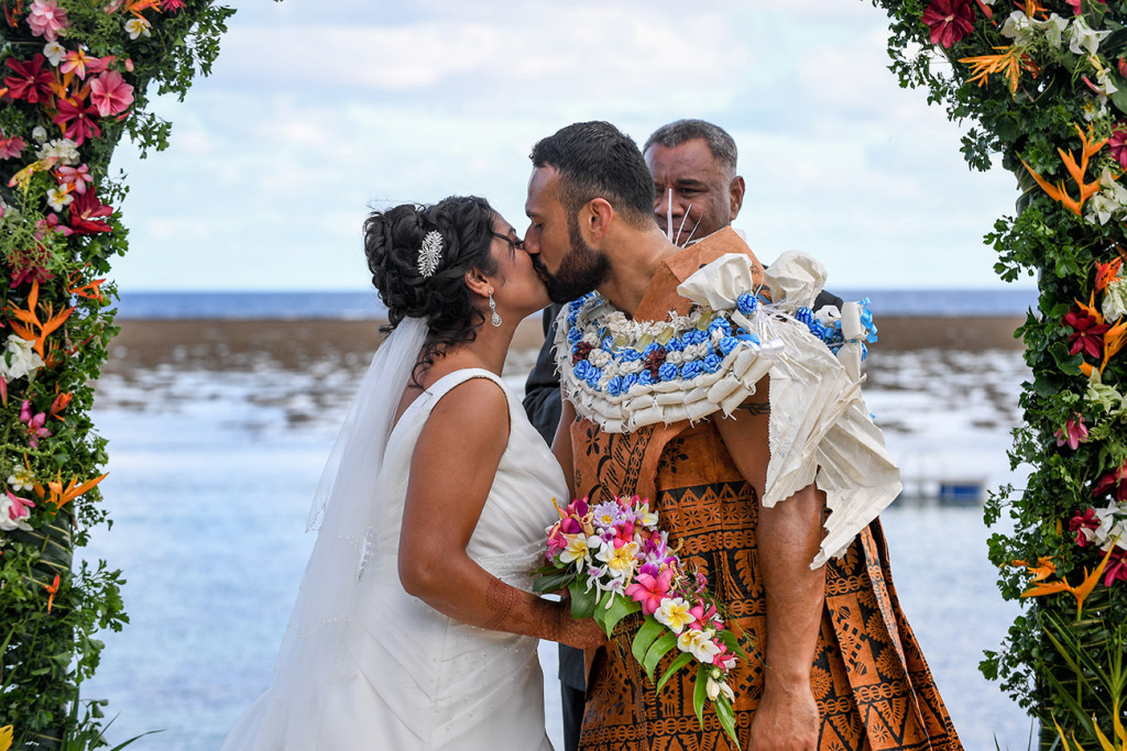 Bride and groom kiss overlooking the sea at Warwick Fiji