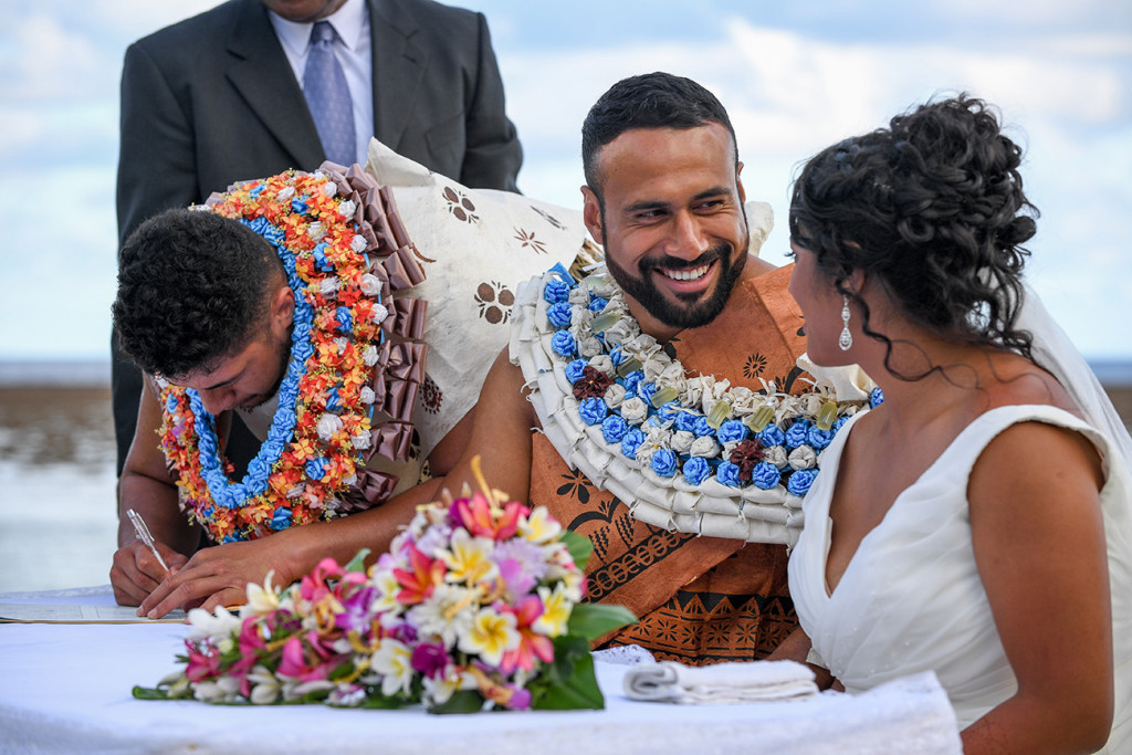 The groom smiles at his bride while his bestman signs the marriage certificate