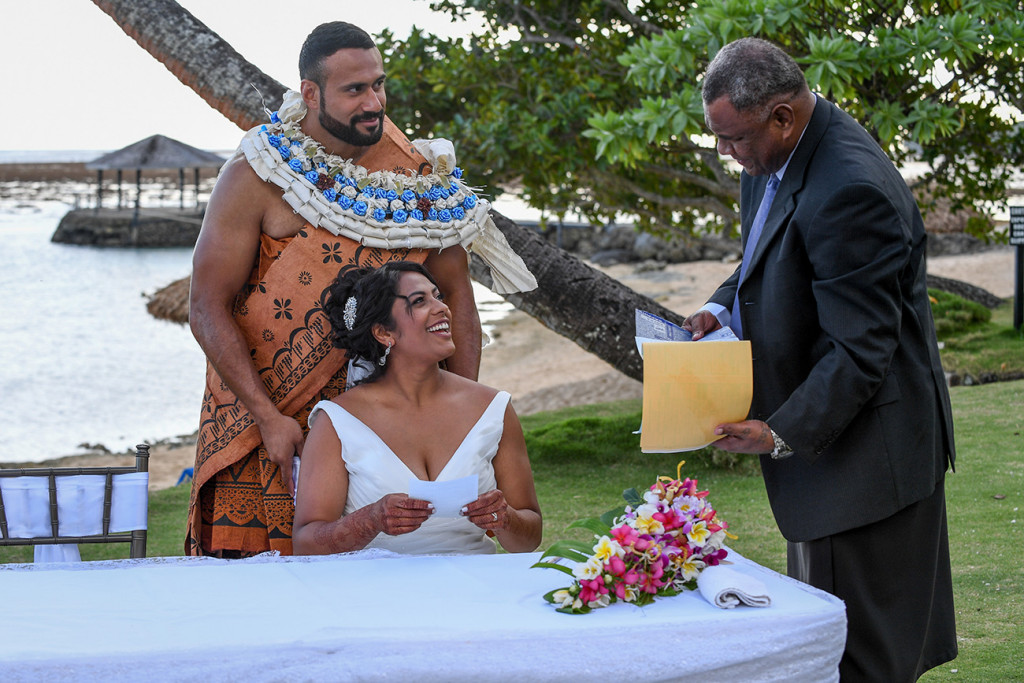 The couple smile at the celebrant who puts the certificate in an envelope