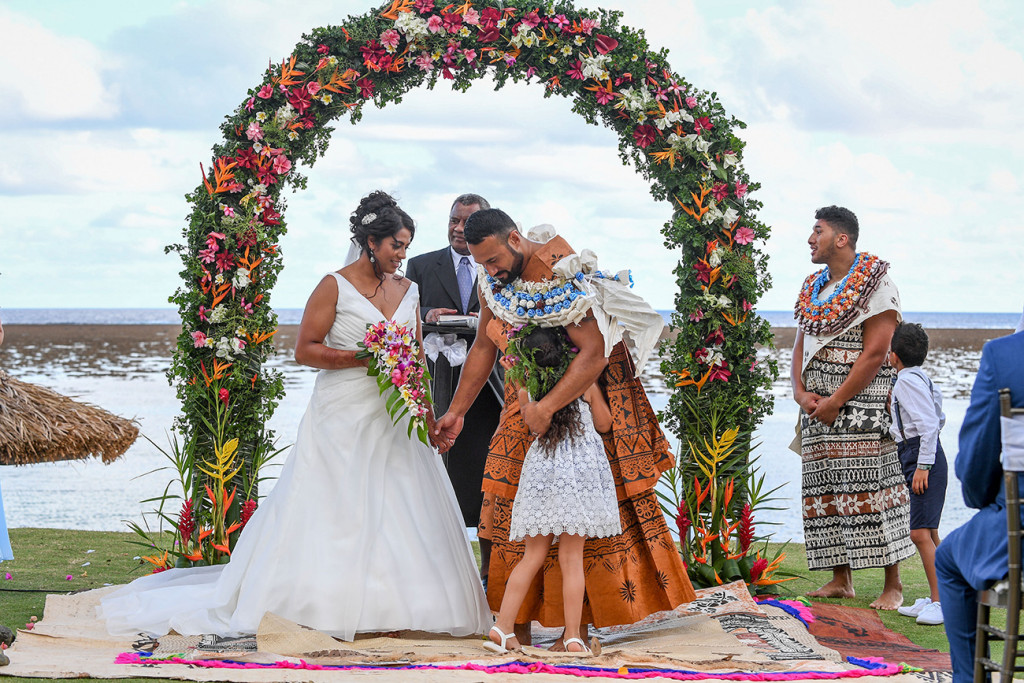 Flowergirl hugs the groom while they are at the altar