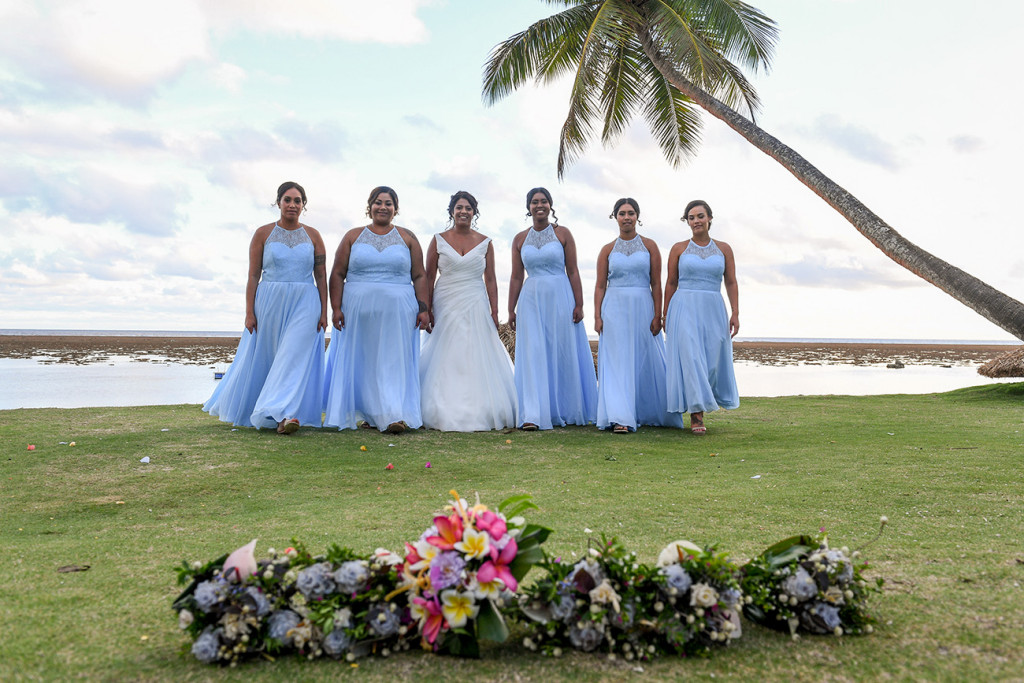 Bride and bridesmaids line up for a photoshoot against palm trees and sea