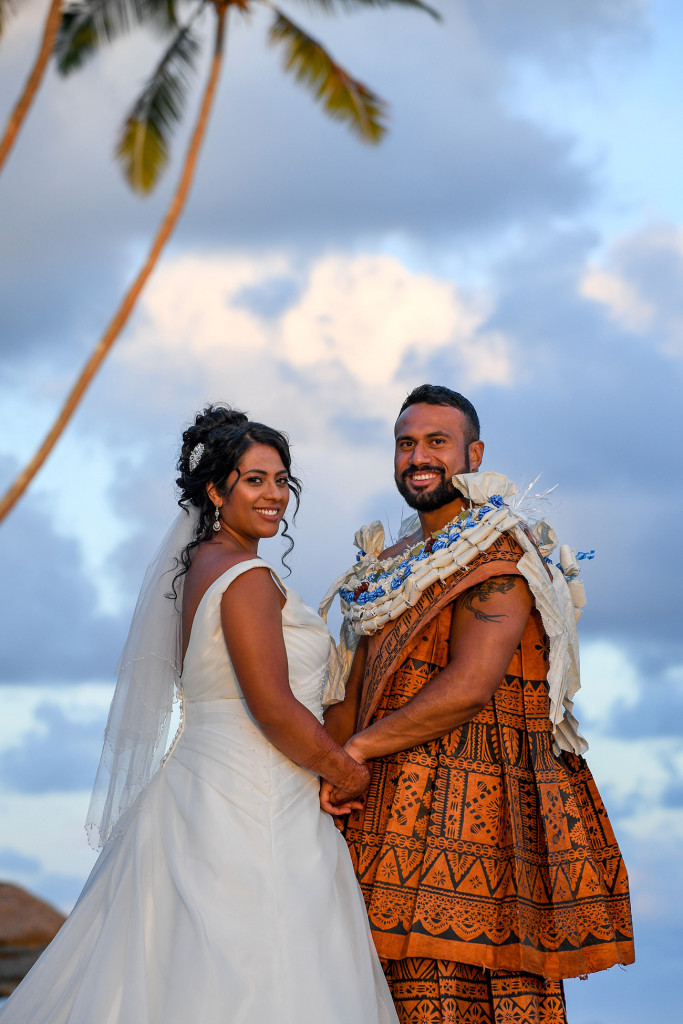 The bride and groom pose for a photo against the baby blue Fiji sky