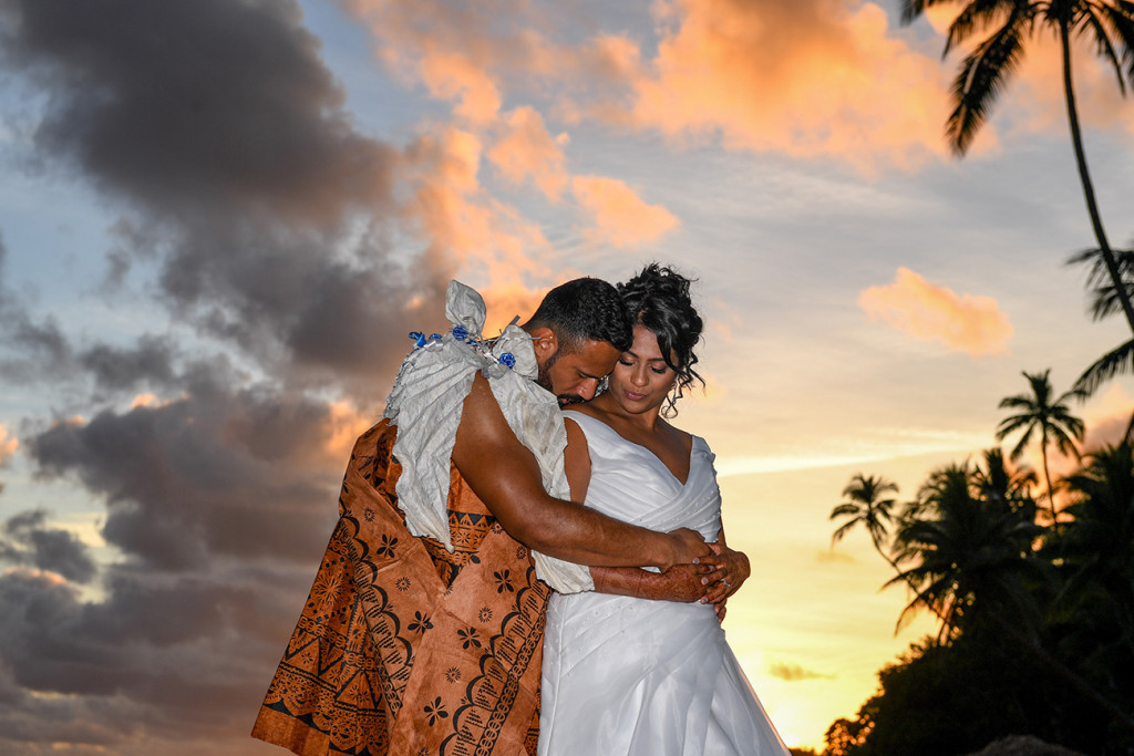 The groom delicately kisses his bride's shoulder in the golden Fiji sunset