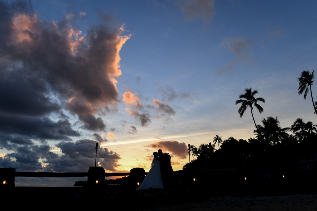 Silhouette of bride and groom kissing in Stunning Fiji sunset over palm trees and Warwick