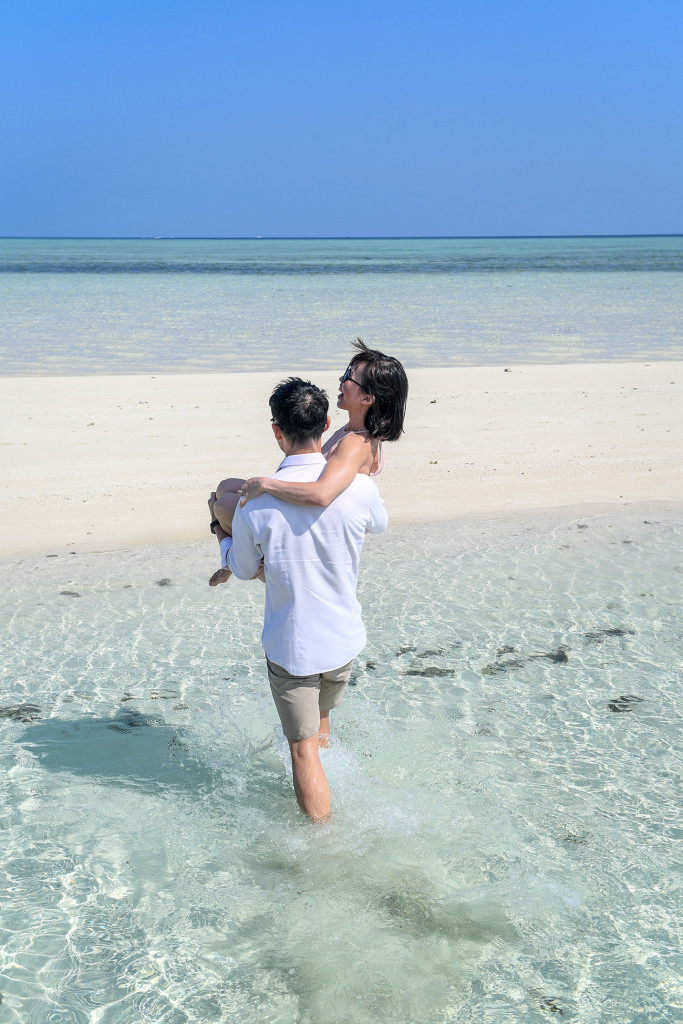 The groom wades into the turquoise clear water carrying his bride