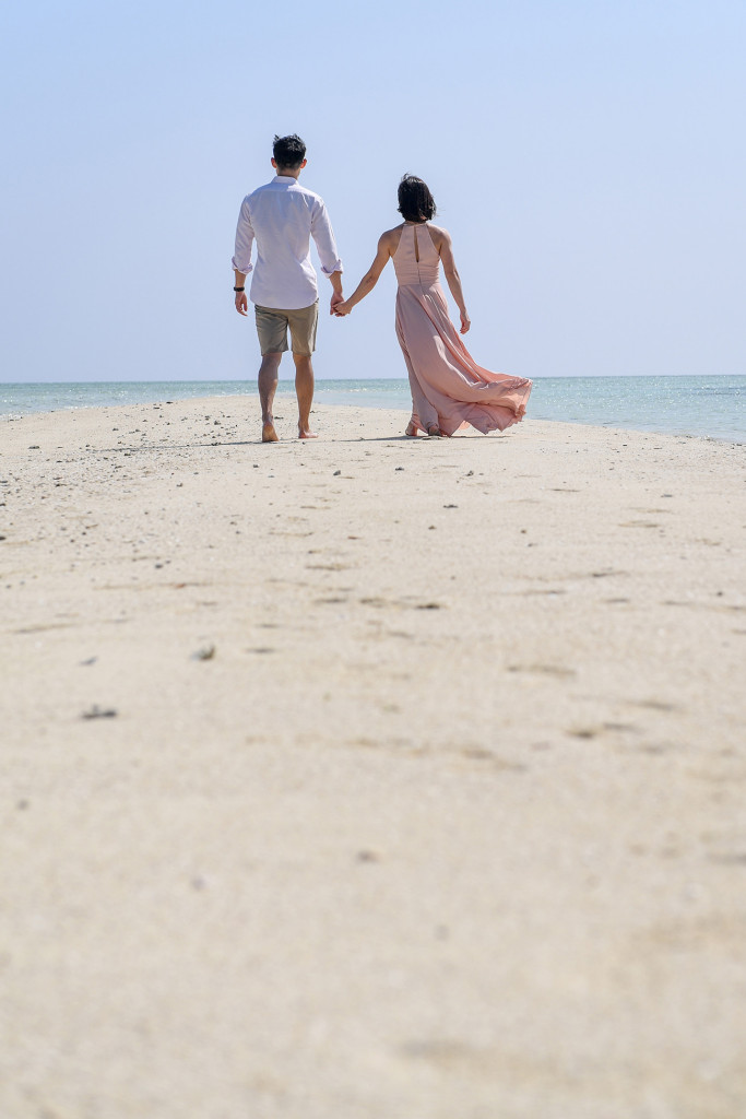 The newly married couple stroll in the reef path on the beach