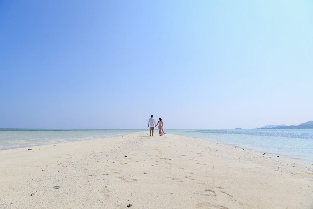 The couple stroll into the horizon of a cloudless blue sky at the reef