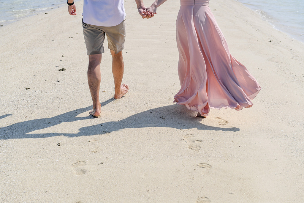 The couple leaves footprints in the stunning white sand at Malolo Lai Island Fiji