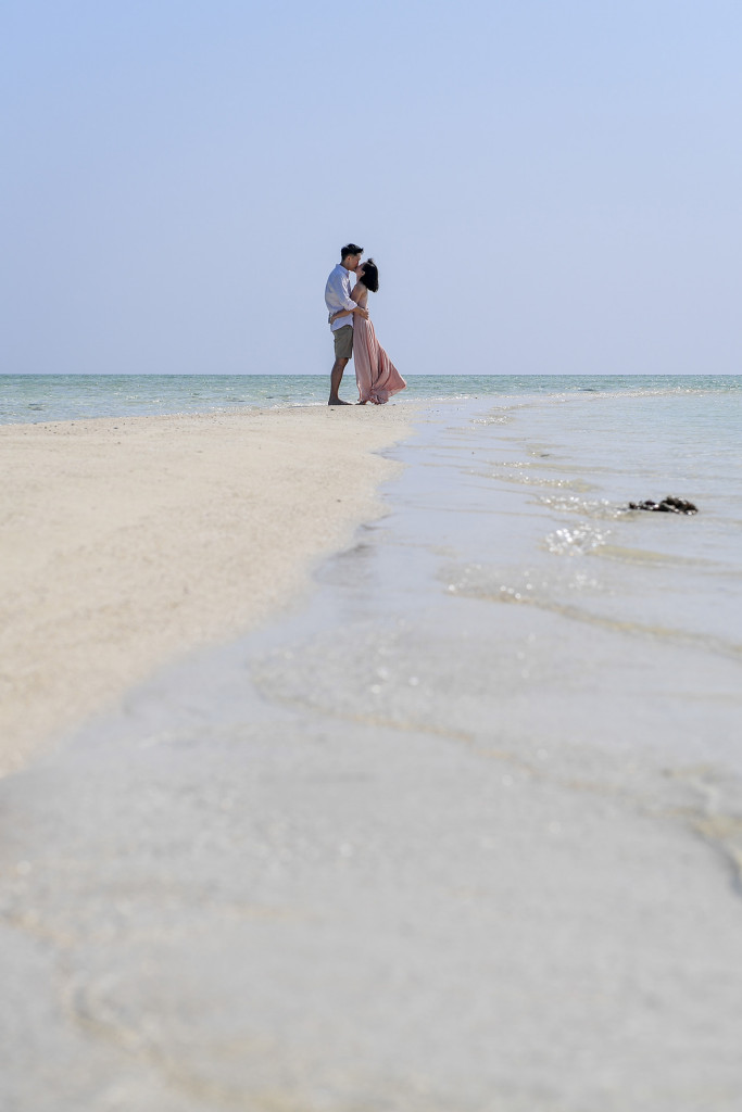 The newly married couple passionately kiss in the horizon at the edge of the reef