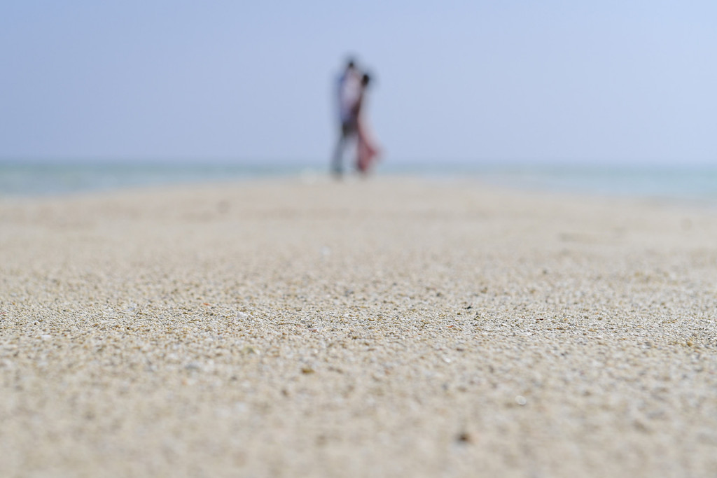 Focus on the fine white sand particles as the couple kisses in the background
