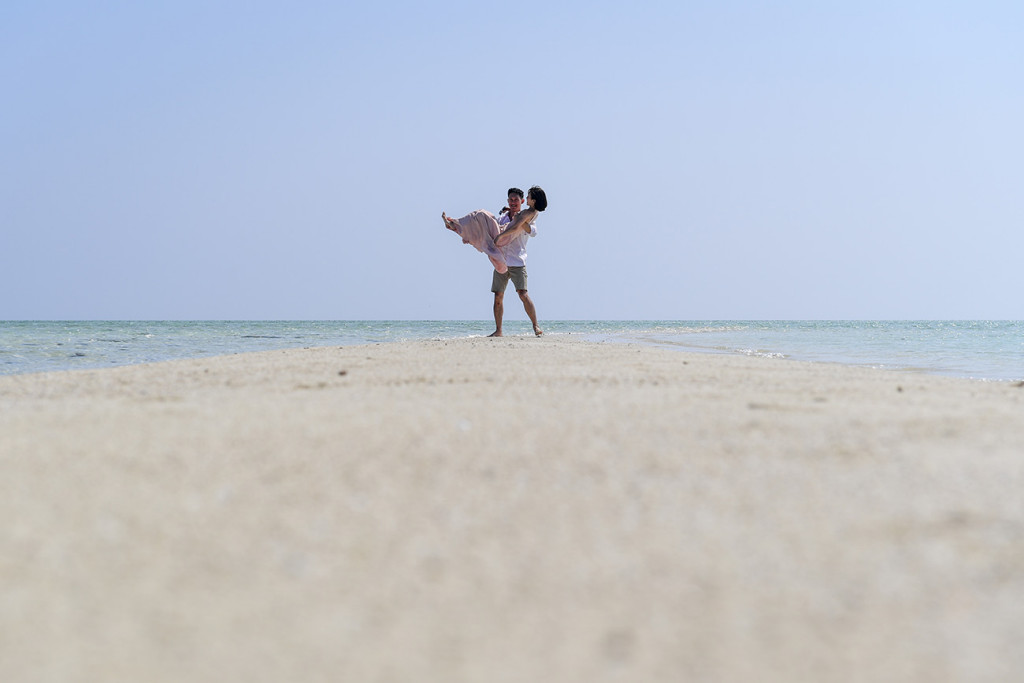 The groom lifts his bride against the cloudless baby blue sky