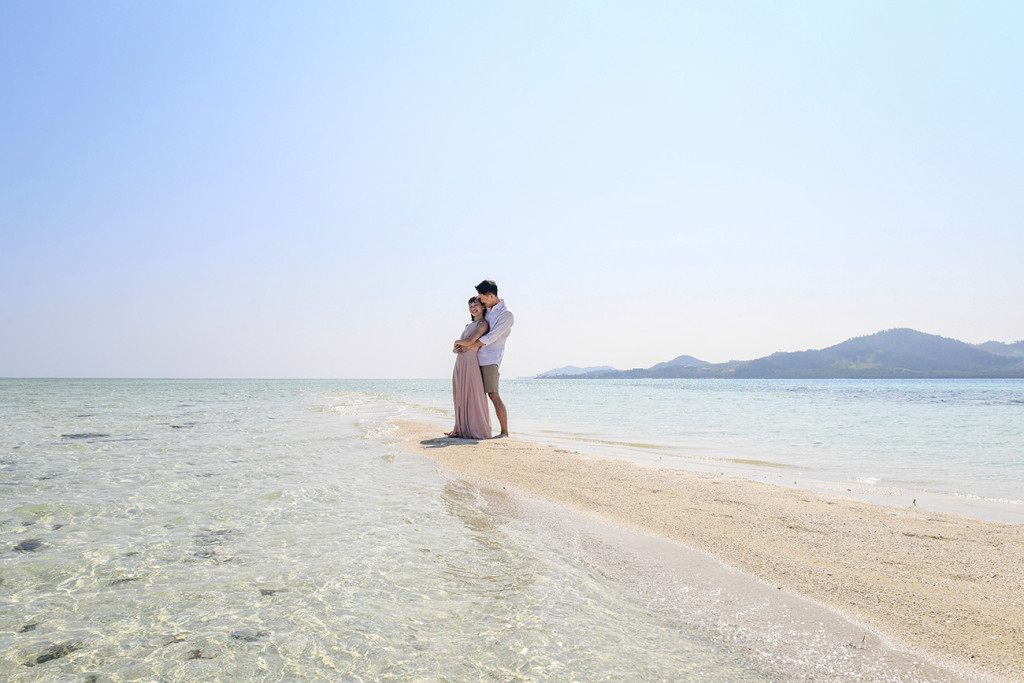 The couple cuddle on the reef with the hills of Malolo Island behind them