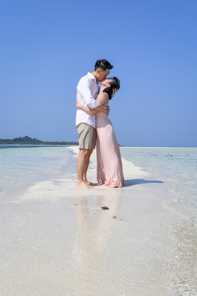 The couple passionately kisses on the reef