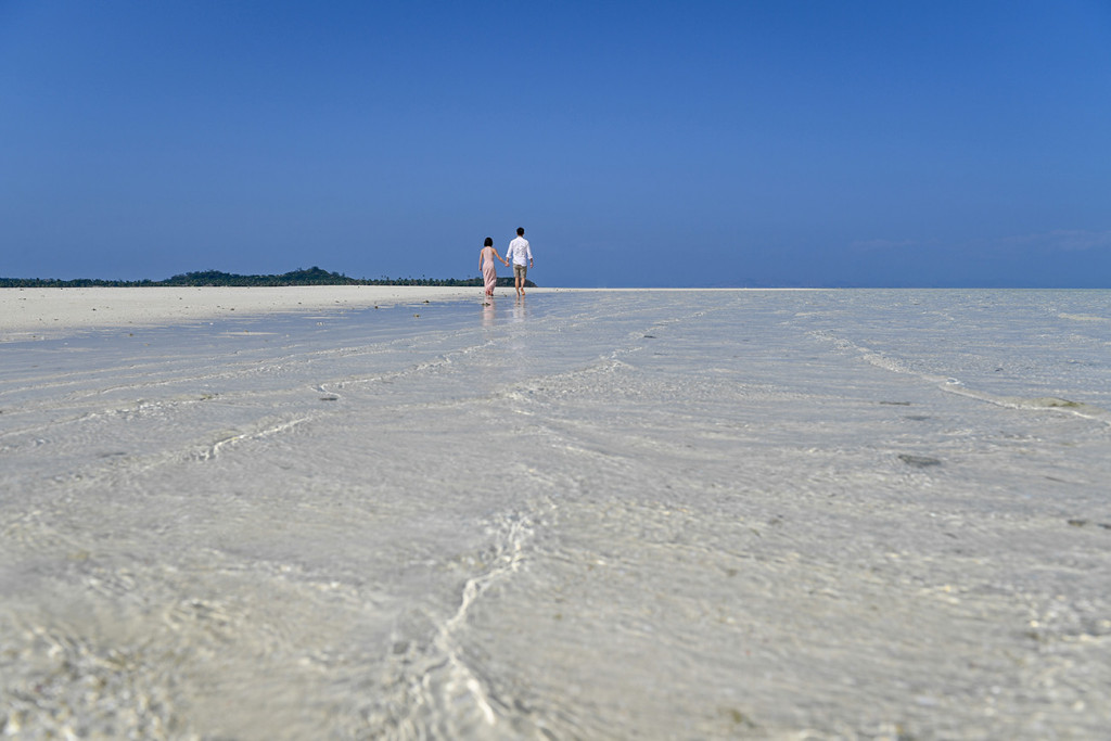 A deep blue cloudless blue sky lies ahead of the couple in the horizon