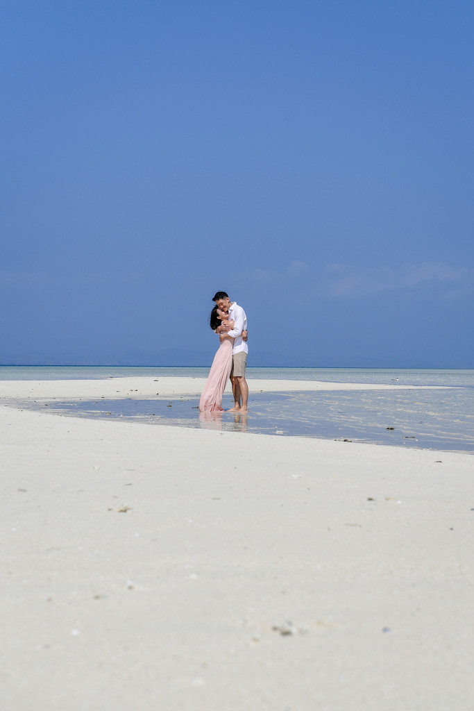 The couple hugs on the shores of the shallow waters of the reef