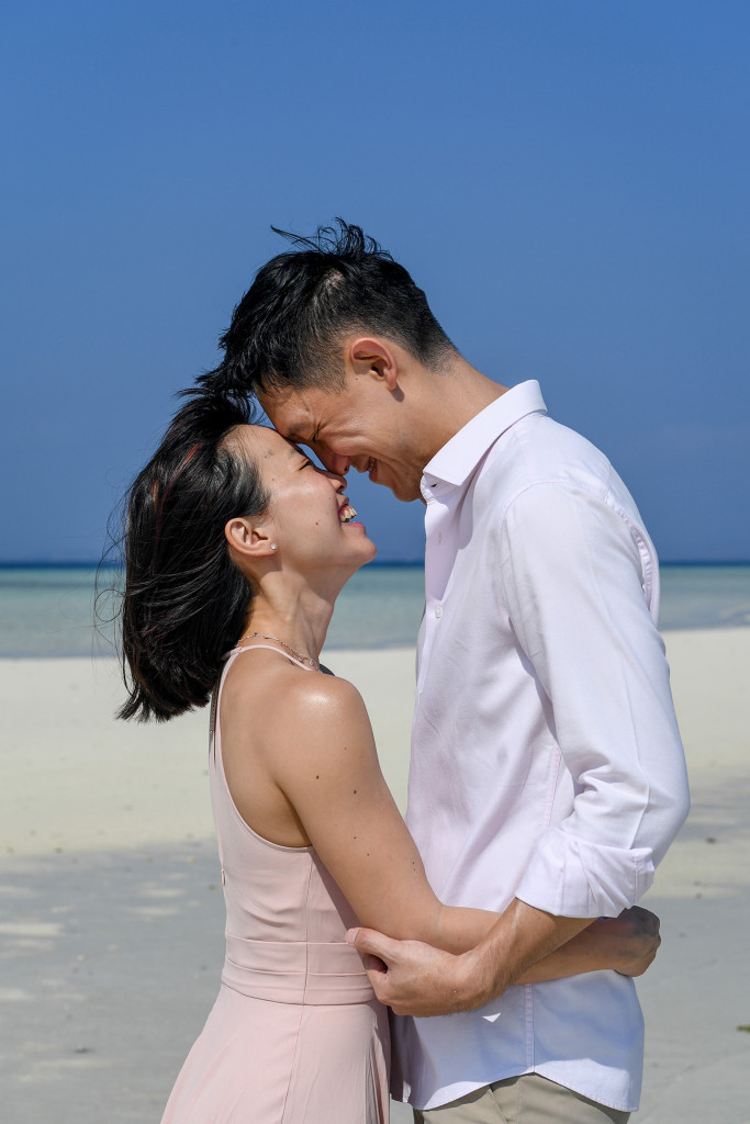 The couple laugh with each other while standing against deep blue skies