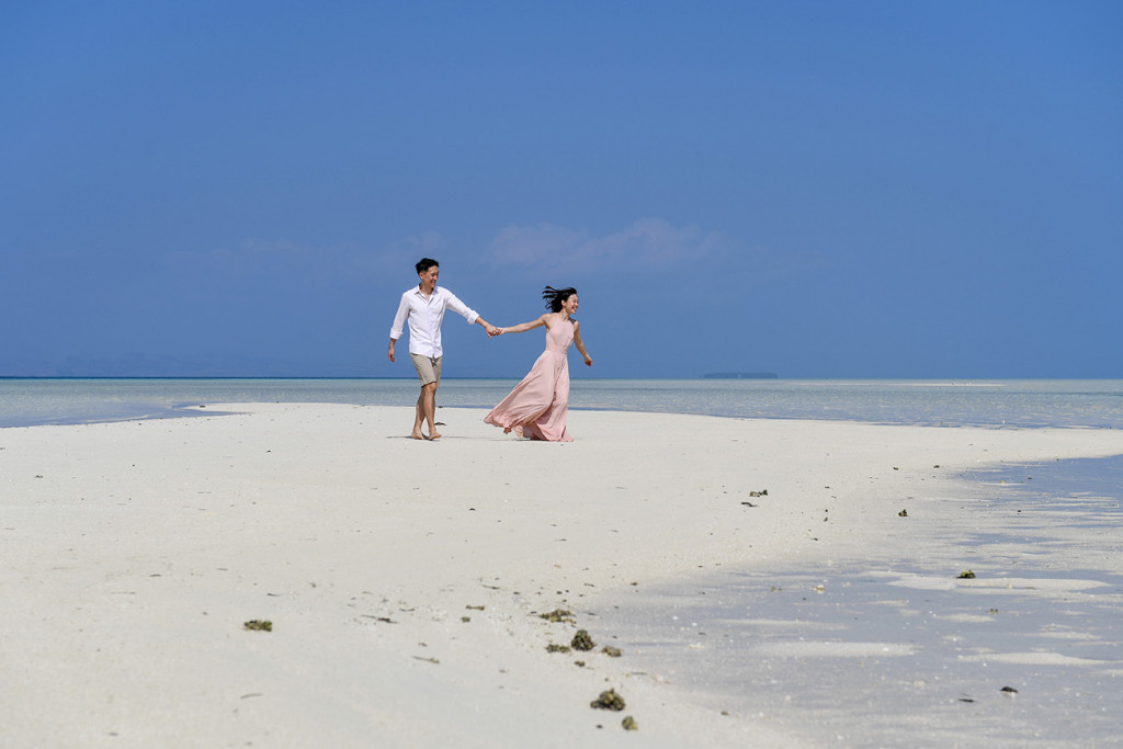 The bride runs towards the sea at Malolo Lai Lai Island with her husband in tow