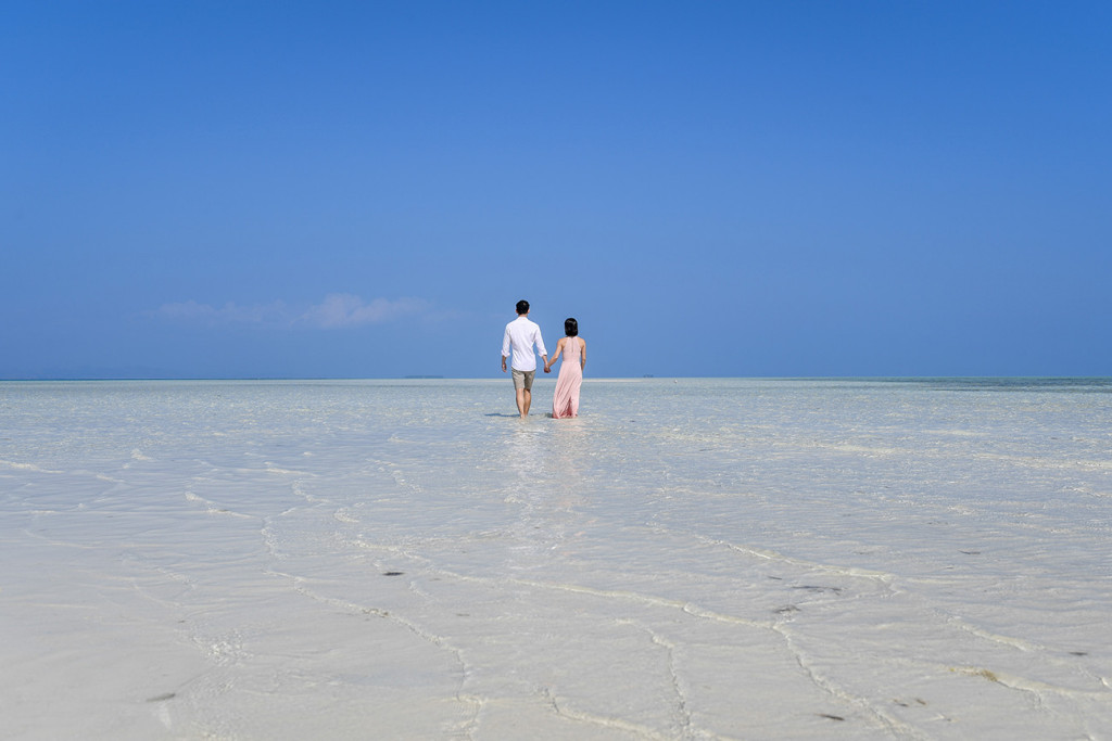 The couple wades in the subsiding waters of Malolo Lai Lai Island at Lomani Island Resort