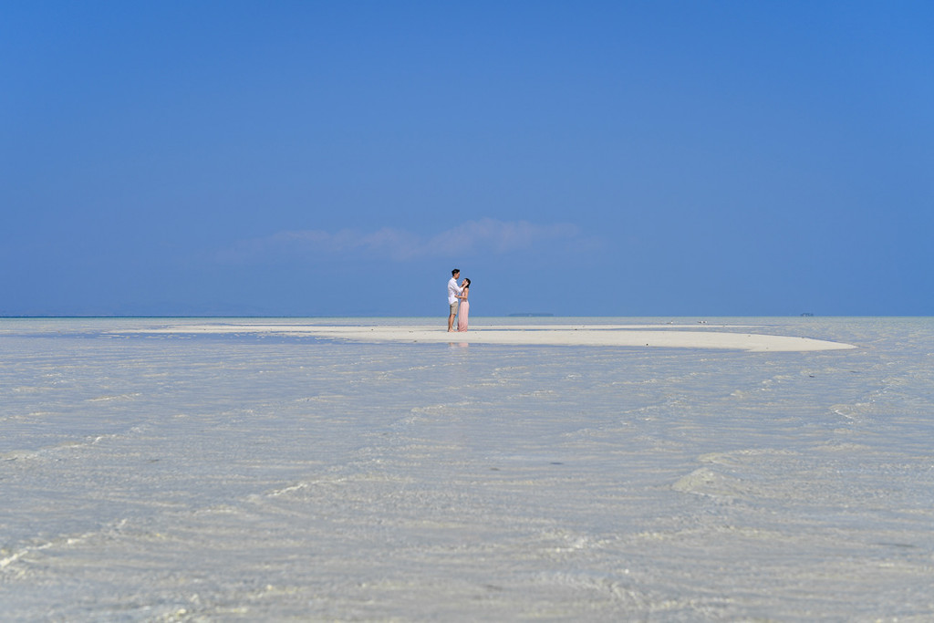 The couple kiss against the deep blue skies at Lomani Island Resort