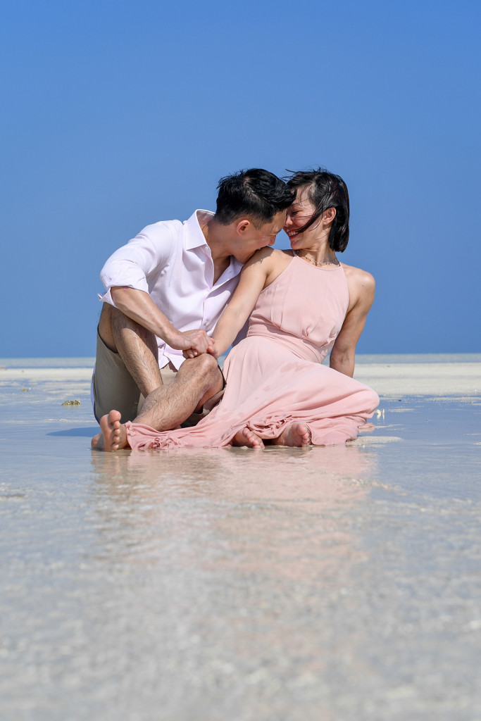 The groom playfully bites his bride's shoulder while seated in the shallow waters of the reef