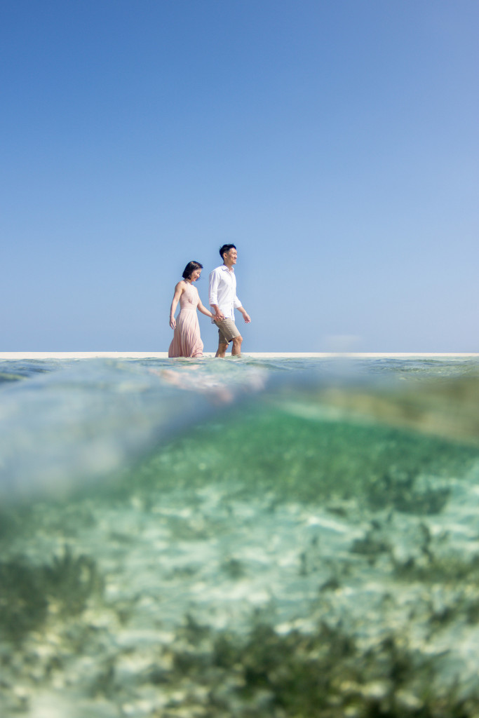 A partial underwater shot of the couple wading into deep waters of the ocean