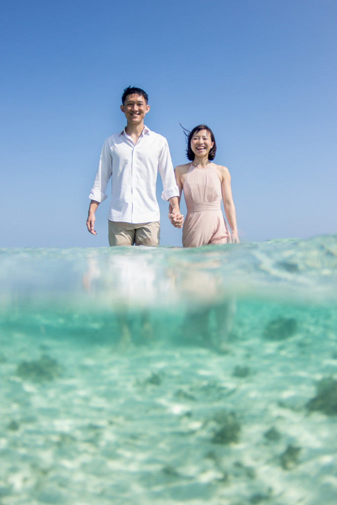 A partial underwater shot of the couple holding hands and strolling towards camera