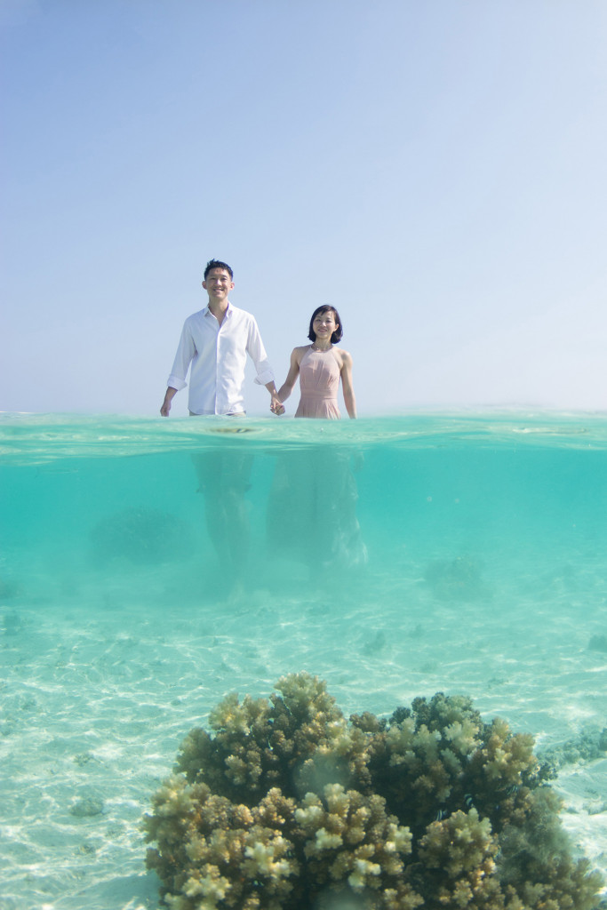 A mid-underwater shot of the couple walking towards a coral