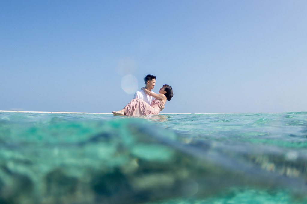 The groom suspends his bride above the surface of the ocean