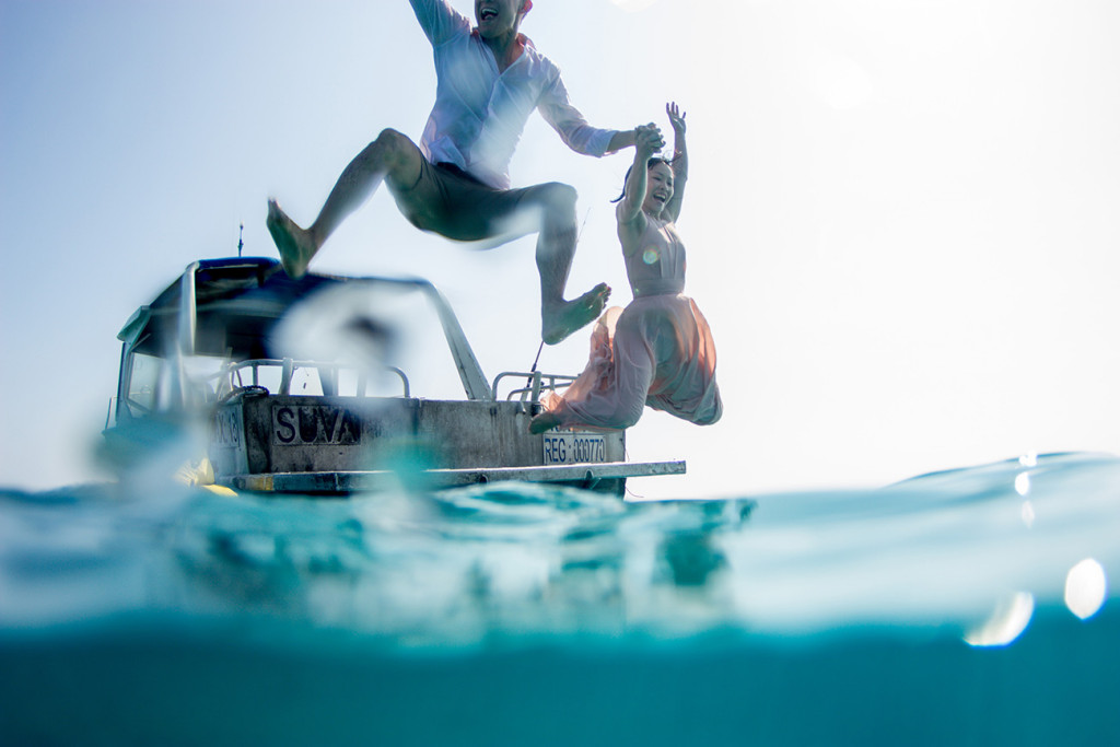 The couple is captured making a gigantic leap into the ocean