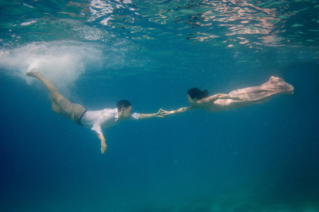 The couple recreates the touch of Adam underwater
