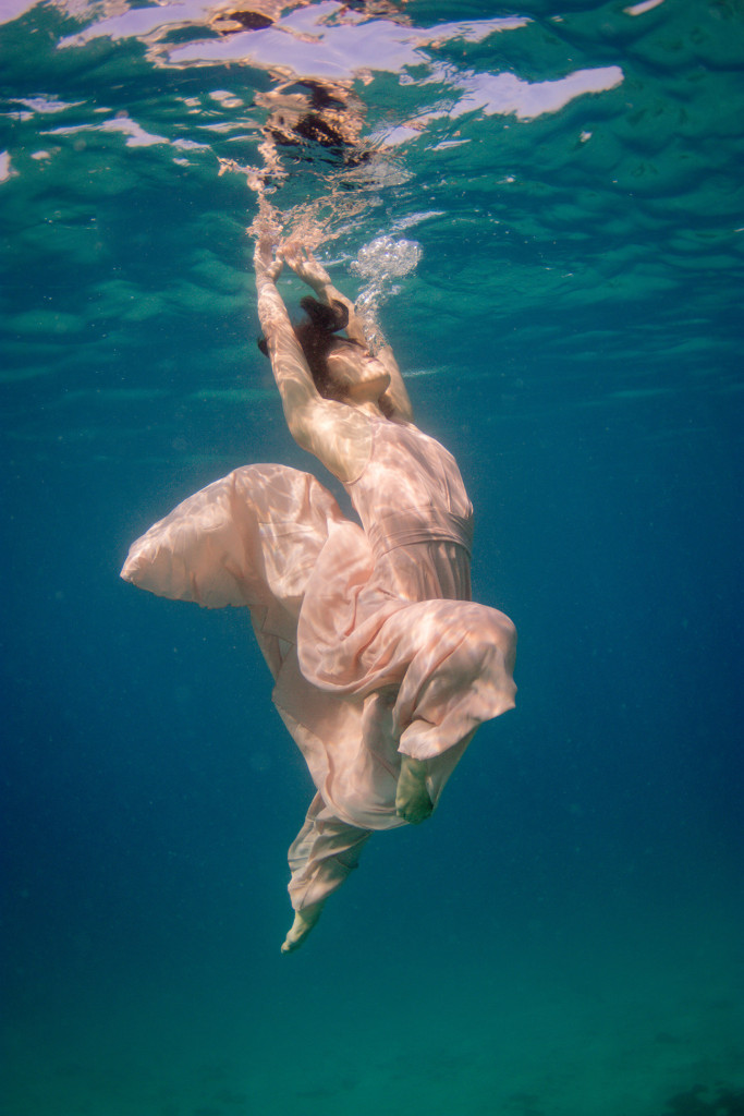 A portrait of the bride gloriously swimming underwater